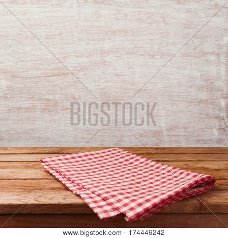 Empty wooden deck table with red cheched tablecloth over rustic wall background for product montage display. Restaurant or kitchen interior