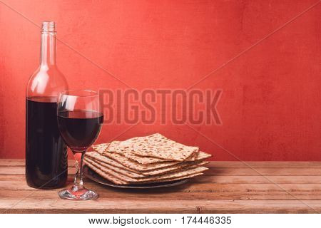 Passover holiday concept with wine glass and matzoh on wooden table over red background