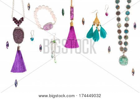 Handmade turquoise and violet bijouterie with gems, tassels and feathers, lying flat on the white horizontal background, top view