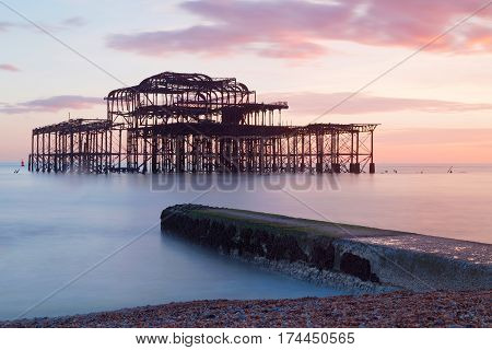 Abandoned West pier in Brighton at sunset warm red colors. Soft water and pebbles in the foreground
