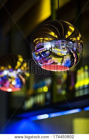 modern bar interior design detail of metallic lampshade with colourful reflections