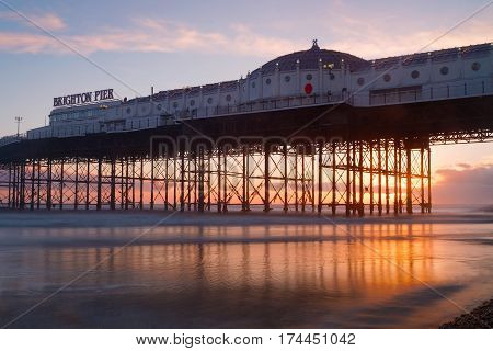 Brighton pier at sunset warm red and orange colors. The pier reflecting in the water