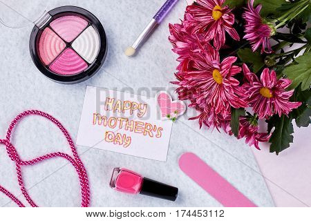 Cosmetics, greeting card and flowers. Congratulation for beloved mother.