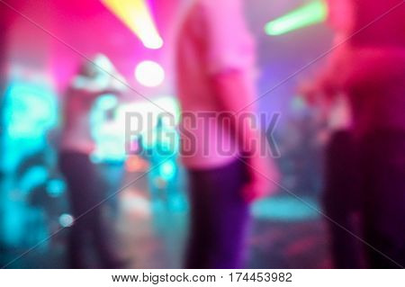 Blurred people dancing with original laser color lights - View of new generation disco club - Defocused image - Concept of nightlife with music entertainment - Warm filter with blurry bokeh
