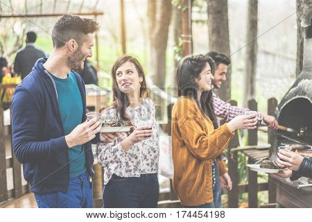 Group of happy friends cooking and eating at barbecue dinner outdoor - Young people toasting wine for bbq in wood house backyard - Friendship concept - Focus on left man face - Warm cinematic filter