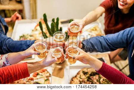 Group of happy friends cheering at home with beer - Young people having fun together eating italian pizza take away - Dinnerparty and friendship concept - Focus on left woman hand