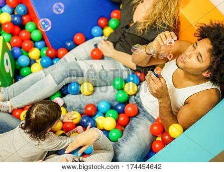 Multi ethnic parents playing with daughter inside ball pit swimming pool - Happy people having fun in children playground indoor - Family and love concept - Focus on man face - Warm filter