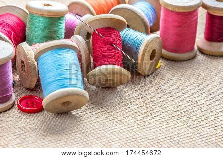 sewing tools (many different colorful thread needle buttons) on wooden background