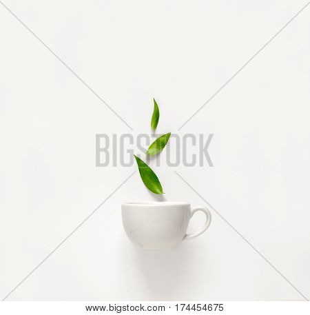 Cup of fresh green tea with green leaves rising above tea aromatic qualities concept