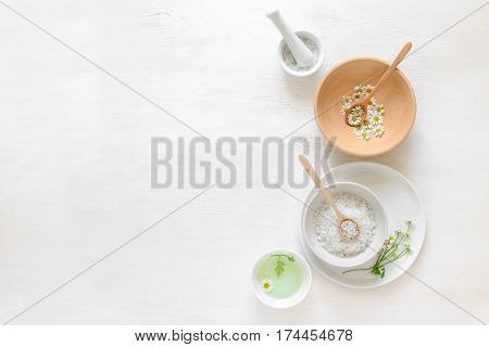 Spa background with various natural cosmetic components and chamomile flowers view from above
