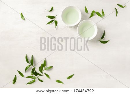 Tea concept two white cups of tea surrounded with green tea leaves view from above spacefor a text