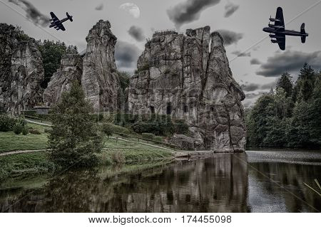 Two old combat aircraft bomber from the World War II flying over the Externsteine. Rock formation in the Teutoburg Forest Germany North Rhine Westphalia.
