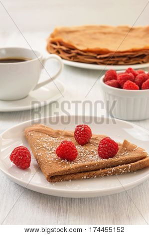 Healthy vegan carob crepes decorated with flaked coconut. Whole wheat chocolate crepes with fresh raspberries on white plate and cup of tea and coffee on white wooden background. Healthy breakfast concept vertical