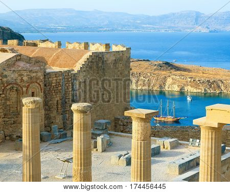 Panoramic view of Doris Temple of Athena Lindia, medieval castle on Acropolis of Lindos with blue bay beneath, Rhodes Island