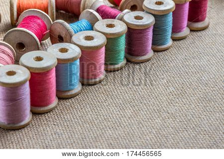 many different colorful thread on wooden background