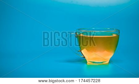 Yellow tea in glass teacup over blue background. Front view