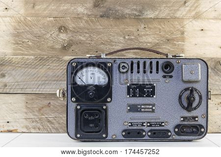 Old vintage electric stabilizer on weathered wooden background. Retro voltage regulator. Wood background