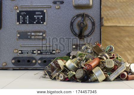 Retro electric stabilizer with transistors, resistors, radio parts wood backgraund. Vintage voltage regulator.