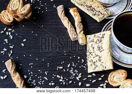 cup of coffee with puff pastries with sunflower seeds sesame seeds and flax