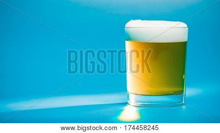 Light beer or ale in low drinking glass over blue background. Front view