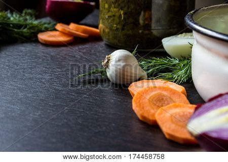 garlic dill cut carrot cut red onion boiled egg near iron tureen and bowl of sorrel on dark wooden table. Small depth of focus