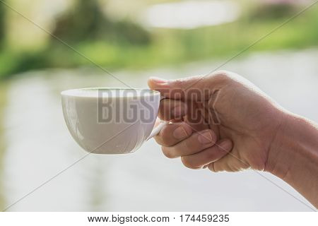 white cup of hot drink in a hand