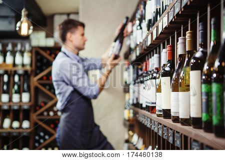 Shelves with elite wine and defocused thoughtful young sommelier holding bottle of red wine in cellar on background reading information on sticker about drink
