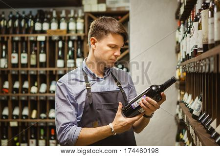 Young sommelier holding bottle of red wine in cellar, reading information on sticker about drink. Thoughtful expert in winemaking on background of shelves with wine