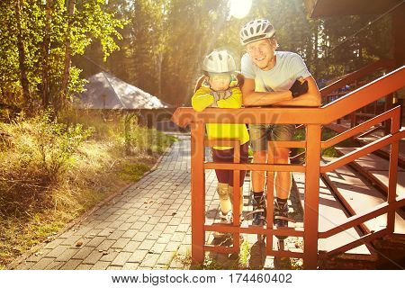 portrait of a sports dad and daughter in a helmet. Dad with his little daughter on the skates. two people rollerblade