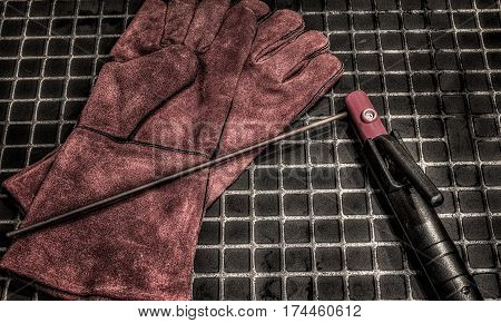 Gloves for welders.Orange leather gloves and electrodes for welding . Accessories of welder.