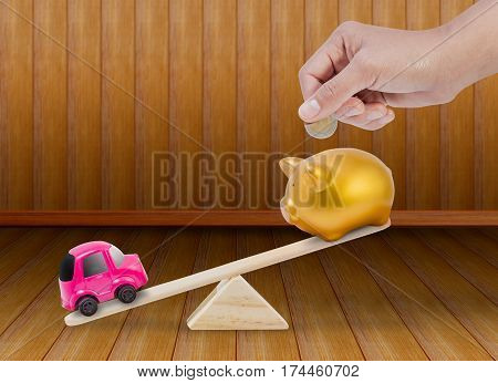Concept about saving to buy the car with The piggy bank and car toy on seesaw.