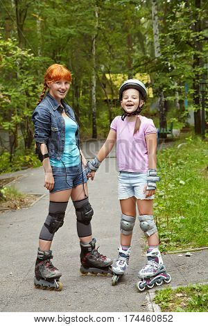sports mother and daughter in a helmet. family on the skates. two people rollerblade. rollerskating outdoor