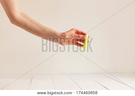 Woman's hand holding clean green cotton tampon