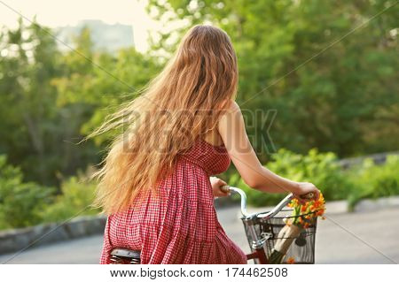 young woman in a dress rides a bike in a summer park. Active people. Outdoors