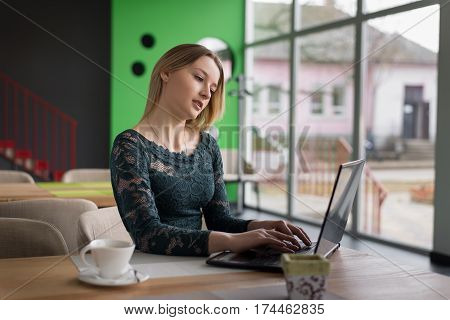 girl typing on laptop sitting in a cafe over a Cup of coffee