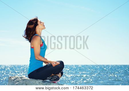 young beautiful woman meditating on the sea shore on a background of water