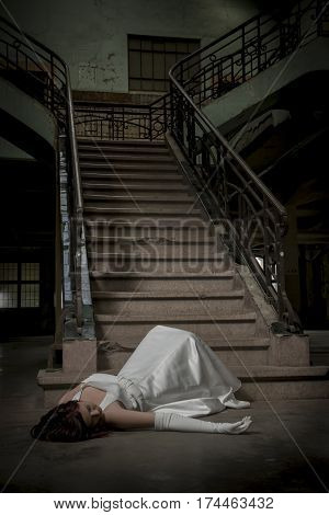 bride's fallen down the stairs by accident and lies unconscious on the ground
