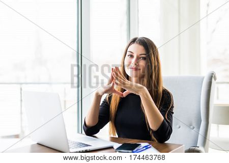 Searching for new solution. Pensive young beautiful businesswoman in glasses working on laptop and keeping hand on chin while sitting at her working place
