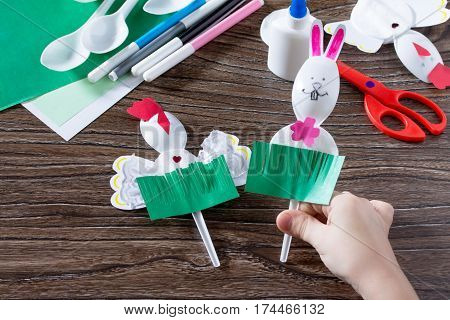 The Child Creates An Easter Gift Toy Easter Bunny. Paper, Glue And Plastic Spoons On A Wooden Table.
