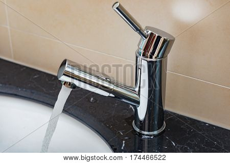 water running out from stainless steel tap to a washbasin in bathroom