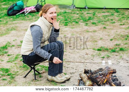 Woman roast marshmallows over a campfire, dressed in trekking clothes sitting on a folding chair beside a campfire. Cooking a delicious dessert on fire during the holiday camping.