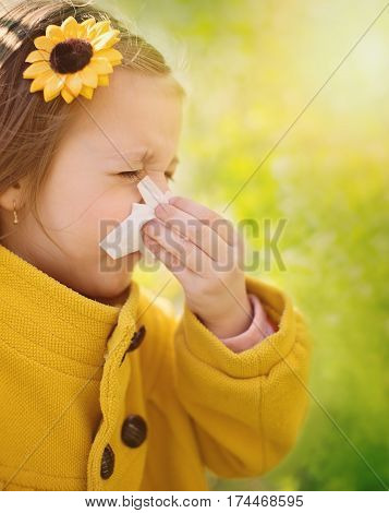 Allergy. Little girl is blowing her nose near spring tree in bloom