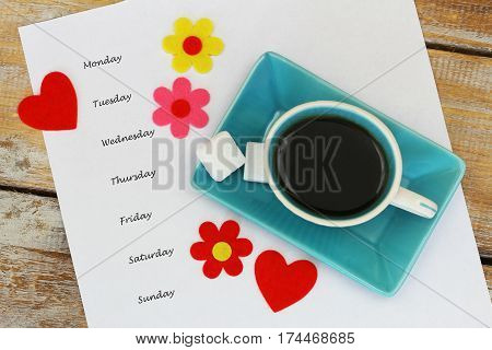 Weekdays written on white piece of paper with cup of coffee, colorful flowers and red hearts