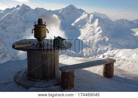 A wooden bench next to a wooden table on which stands the hot samovar teapot cup of tea. Against snowy mountain peaks.