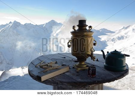 Wooden table on which stands the hot samovar teapot cup of tea. Against snowy mountain peaks.