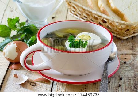 Soup With Fresh Nettles, Egg, Meat And Potatoes. Fresh Nettle Leaf On The Kitchen Table A Rustic Bac
