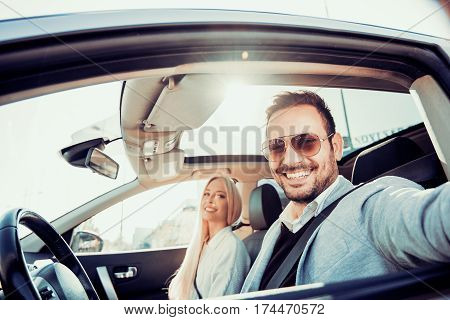 Enjoying road trip together.Happy young couple having fun while riding in their car.