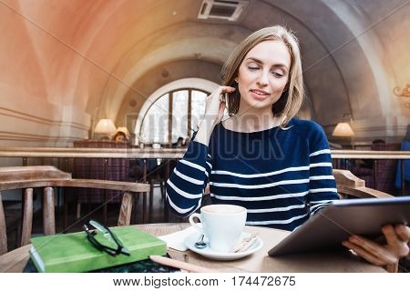 A smile young woman in the cafe with a cup of coffee looking at the digital tablet. Young girl with a cup of coffee and reading viewing internet in tablet while relaxing in cafe.