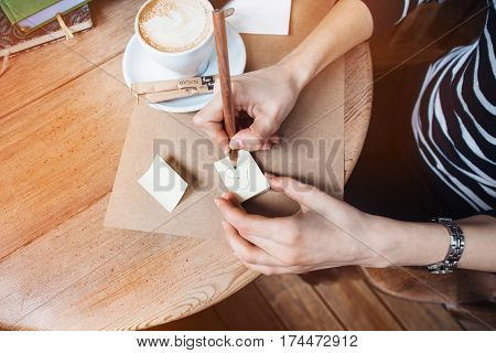 Close up of woman hands writing love notes stickies by wooden pencil. Young beautiful woman drawing love message for a boy friend in a cafe. View from above.