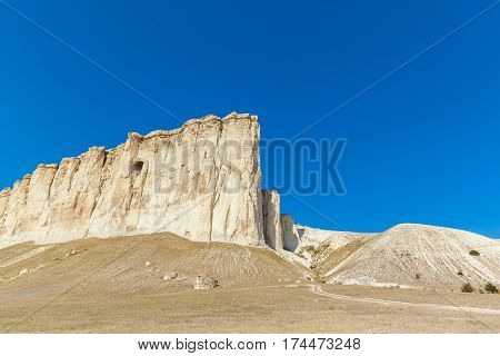 View of White rock or Aq Qaya on a Sunny summer day. Crimea. White limestone with a vertical cliff